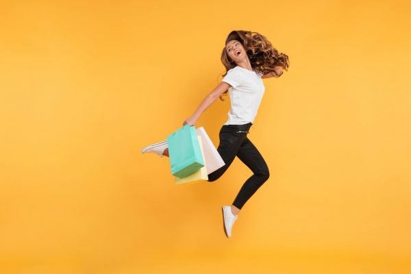 laughing-pretty-young-woman-jumping-holding-shopping-bags (1)